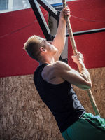 Handsome young man climbing rope in gym