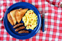 High angle shot of country style scrambled eggs with peppers, sausage and toast