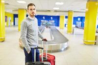 Mann als Passagier wartet an der Gepäckförderanlage