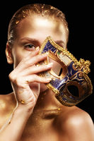 Female with masquerade venecian mask in hand near face. Golden girl on black background