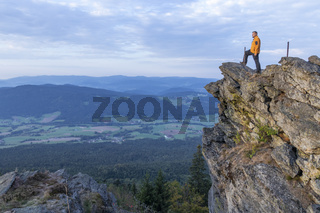 Man goes to a ledge in the Bavarian Forest.