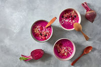 Ceramic handmade bowls with useful red smoothies for breakfast on a concrete background with beets, flat lay