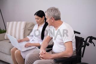 Nurse showing something to patient via laptop.