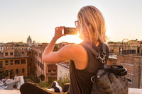 Female tourist taking mobile phone photo of Piazza di Spagna, landmark square with Spanish steps in Rome, Italy at sunset.