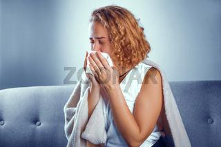 Sick blonde girl sneeses.