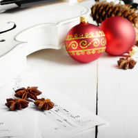 Close view of a violin musical notes and red christmas decoration balls on white wooden table