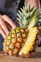 The girl's hands are holding a sliced tropical pineapple with green leaves on on a wooden board. Healthy fruit for dessert