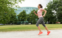 woman with earphones running at park