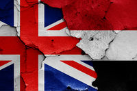 flags of UK and Yemen painted on cracked wall