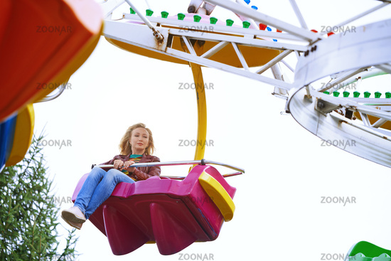 Scared or boring woman riding on rollercoaster