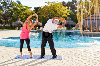 Senioren Paar am Pool macht Stretching
