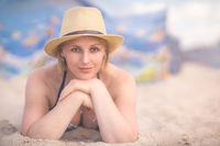 Beautiful woman with a wicker hat on the beach