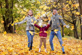 happy family playing with autumn leaves at park