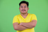 Young handsome overweight Asian man with arms crossed