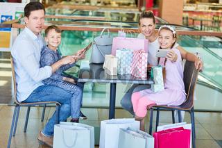 Familie mit Einkaufstüten und Smartphone
