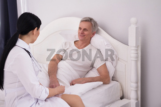Nurse assisting disabled man.