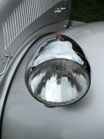 close up of the headlamp of an elegant silver colored stylish 1930s vintage automobile