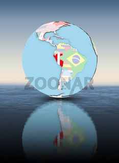 Peru on globe with flags above water surface