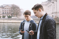 two mobile phone addicted male teenagers standing together looking at smartphone