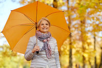 happy senior woman with umbrella at autumn park