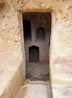 a narrow door carved into rock with steps leading to dark underground chambers at the tombs of the kings in paphos cyprus