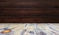 old painted washed oak wood table on the blurry brown wood wall background, wooden table.