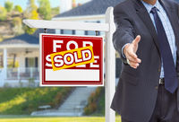 Male Agent Reaching for Hand Shake in Front of Sold For Sale Sign and House