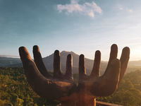 Hand shaped sculpture with Batur volcano during beautiful sunrise in Bali