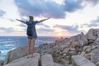 Female traveler, arms rised to the sky, watches a beautiful sunset on spectacular rocks of Capo Testa, Sardinia, Italy.