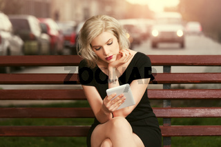 Young fashion blond woman with tablet computer sitting on bench