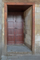 Recessed wooden aged engraved door and stone wall