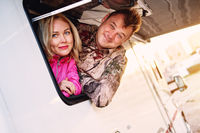 Married middle-aged couple family wife and husband getting out from caravan recreational vehicle motor home trailer window looking at camera feels happy and satisfied. Tourism and trip concept