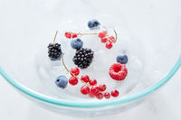 Close-up blackberries, blueberries,raspberries, currants and ice cubes in a glass transparent bowl on a gray marble background . Top view