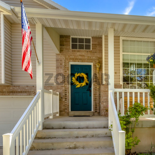 Square frame Stairs leading to the porch and front door of a home with a lovely garden