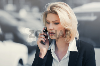 Young fashion business woman calling on cell phone in city street