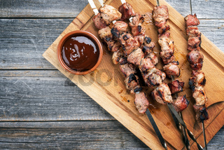 Traditional Russian shashlik on a barbecue skewer with ketchup as top view on cutting board with copy space left