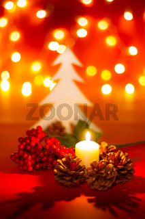 Christmas candle and ornaments over dark background with lights