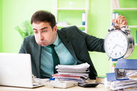 Businessman angry with excessive work sitting in the office in t