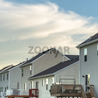 Square frame Row of homes with grassy yards balconies outdoor stairs and white fences