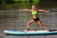 Young attractive woman on SUP in yoga pose on pond