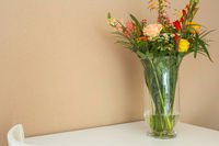 Beautiful flower bouquet on white table with light brown wall, space for text