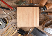 High angle closeup of a large group of tools arranged around an piece of wood, an ideal space for your copy