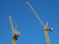 two tall yellow tower cranes working on a construction site against a blue sky