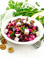 Salad with beetroot and feta in plate on board