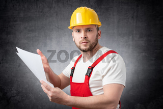 Angry construction worker holding papers