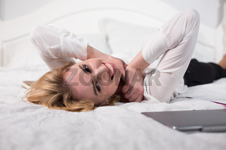 smiling young businesswoman lying on bed