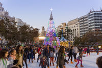 Christmas fair with people ice skating on Modernisme Plaza of the City Hall of Valencia, Spain.