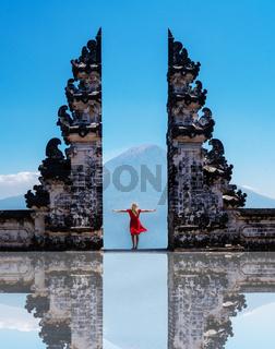 Woman traveler standing at the ancient gates of Pura Luhur Lempuyang temple aka Gates of Heaven in Bali
