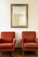 Two chairs and golden framed mirror on a white wall with soft natural light coming in from outside. beauty