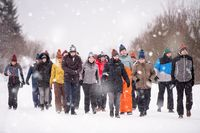 group of young people walking through beautiful winter landscape